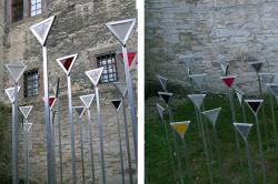 30 Stelen im Burggraben der Wewelsburg mit verschieden farbigen Dreiecken, sogenannte Winkel, die Häftlinge tragen mussten